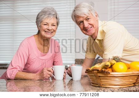 Senior couple having coffee together at home in the kitchen