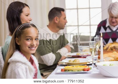 Portrait of a smiling girl at christmas dinner at home in the living room