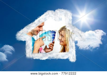 Cute couple chosing colours for painting house against bright blue sky with clouds