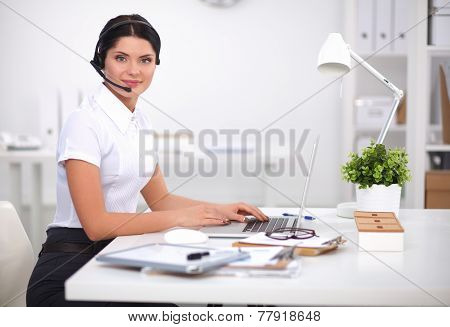 Portrait of beautiful businesswoman working at her desk with headset and laptop