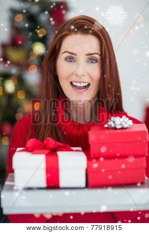 Festive redhead holding pile of gifts against snow falling