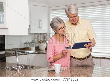 Senior couple shopping online with tablet pc at home in the kitchen