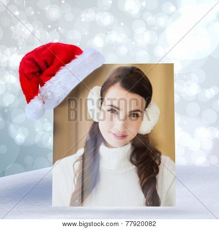 Pretty brunette with ear muffs smiling at camera against light glowing dots design pattern
