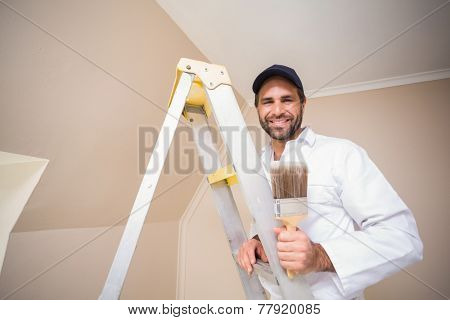 Painter smiling standing on ladder in a new house