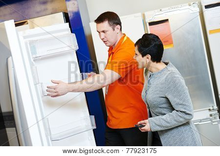 shop assistant demonstrates refrigerator to young woman in home appliance shopping mall supermarket