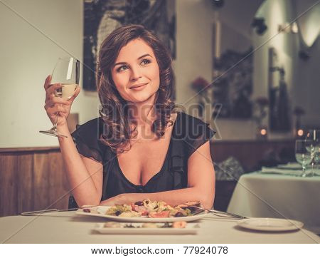 Beautiful young lady alone in restaurant