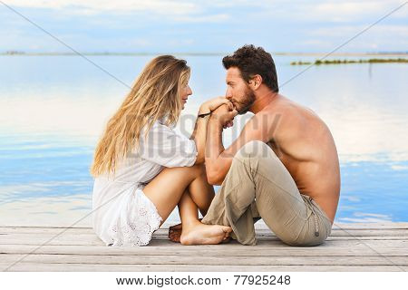 Couple Sitting On A Jetty Under A Blue Sky At A Sunset