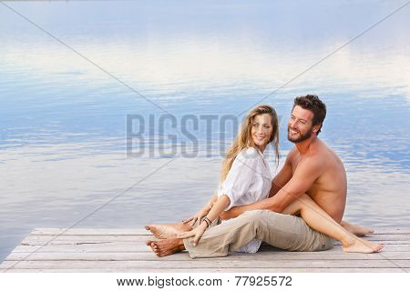 Man And Woman Couple Sitting On A Jetty At A Seaside
