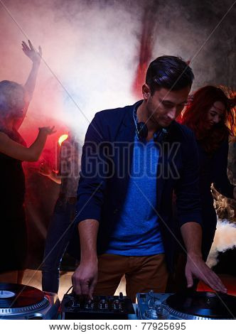 Young stylish man working as deejay in night club