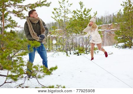 Young guy and his girlfriend playing snowballs outdoors