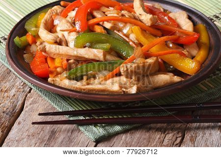 Chicken With Vegetables Close-up And Chopsticks On The Wooden Table