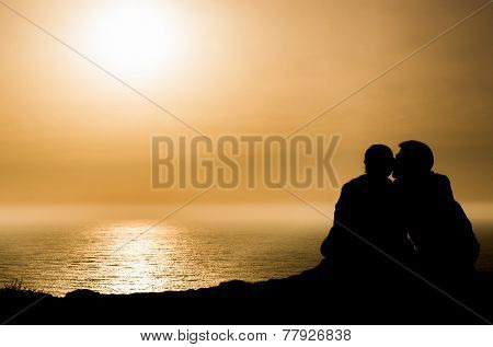 An loving couple sitting arm in arm at Portugal's cliff coast watching the sunset