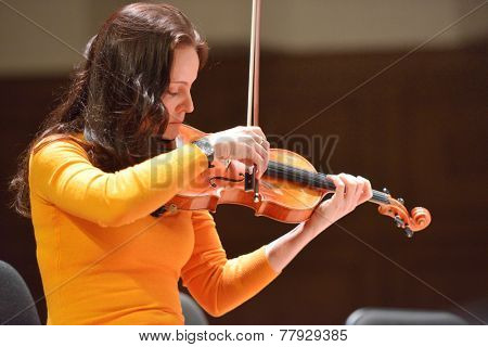 NOVOSIBIRSK, RUSSIA - DECEMBER 5, 2014: First violin of the ensemble Moscow Soloists Arina Shevliakova on the rehearsal during the festival Classics. The festival joins concerts of World music stars