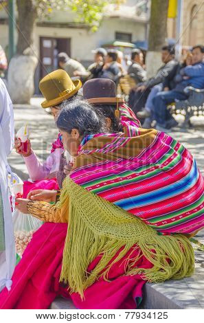 LA PAZ, BOLIVIA, MAY 8, 2014:  Local women in traditional attire rest at Plaza Murillo
