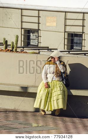 LA PAZ, BOLIVIA, MAY 8, 2014:  Local woman in traditional attire rests sitting on wall