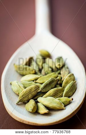 Whole cardamom in wooden spoon  on brown background