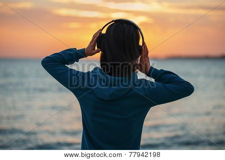 Woman In Headphones Enjoying Sunset Over The Sea