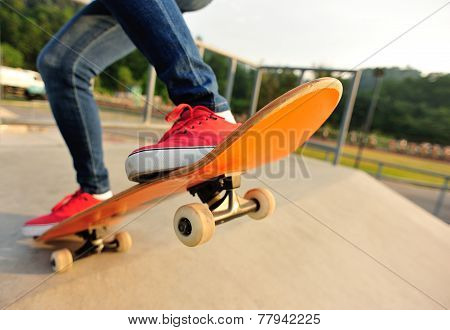 young woman legs skateboarding at skatepark