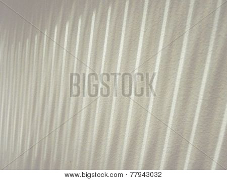 Linear light pattern from vertical blinds on gritty wall..