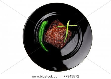 meat food : roast beef fillet mignon served on black plate with chili pepper isolated over white background