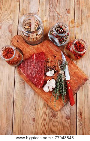 fresh raw beef meat fillet flesh with peppercorn and thyme ready to grill on wood figured old style board  over table with spices in glass