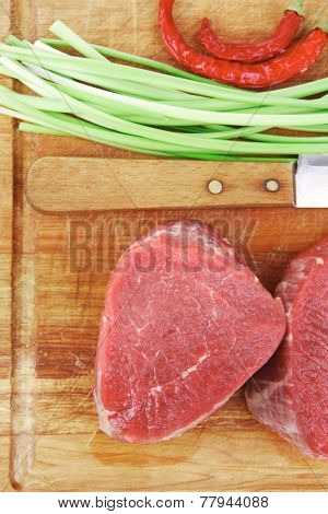 raw meat : fresh beef fillet with thyme and red hot dry pepper on wooden plate . isolated over white background