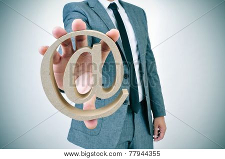 a young businessman showing an at sign in his hand
