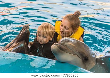 Boy And Mum Float With Dolphins