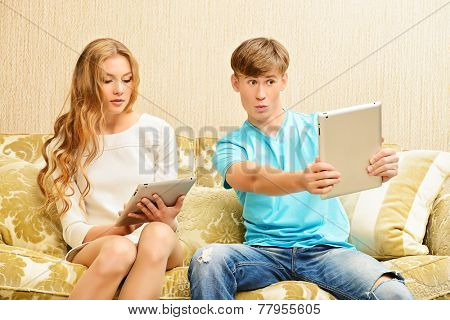 Young woman and a man sitting on a sofa and each of them looks at his own digital tablet. Relationships. Lack of of live communication.
