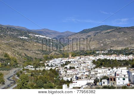 View of white village with the Sierra Nevada mountains to the rear Cadiar Las Alpujarras Granada Pro