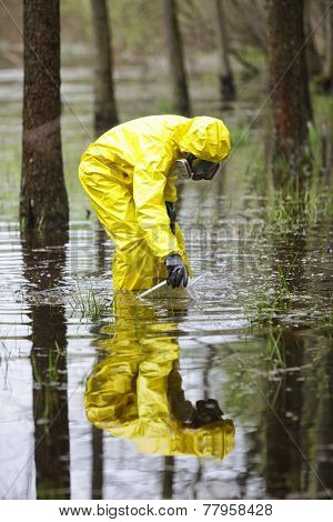 professional in protective coveralls taking sample of water to container in floods contaminated area