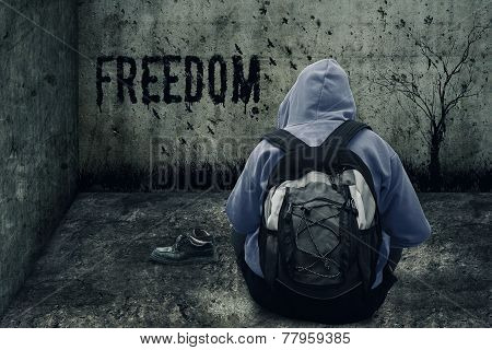 abandoned man drawing freedom on the wall in a closed grunge room