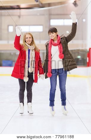 people, women, friendship, sport and leisure concept - two happy girls friends waving hands on skating rink
