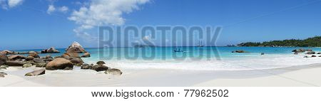 On The Beach In Front Of The Seychelles White Sail Boat Sails On The Blue Sea