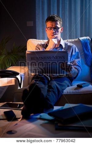 Businessman Reading Newspaper Late At Night