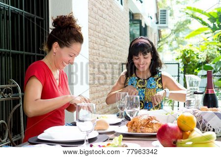 Two beautiful hispanic women enjoying an outdoor home meal together. Concept of family togetherness and outdoor dining.