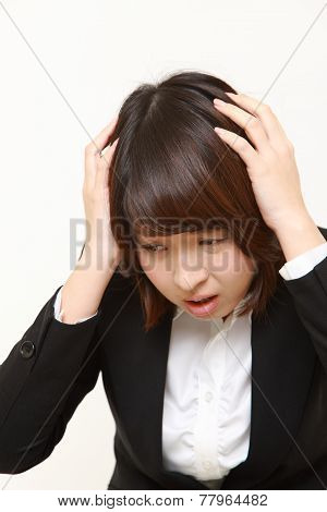 portrait of frustrated young businesswoman pulling her hair