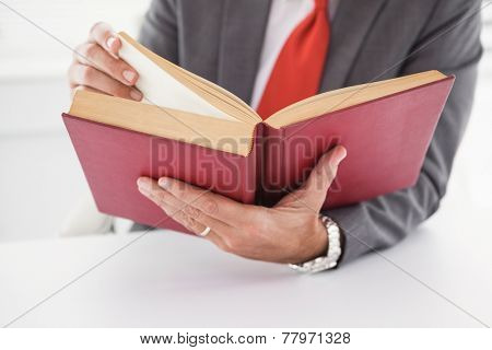 Businessman sitting at desk reading book in his office