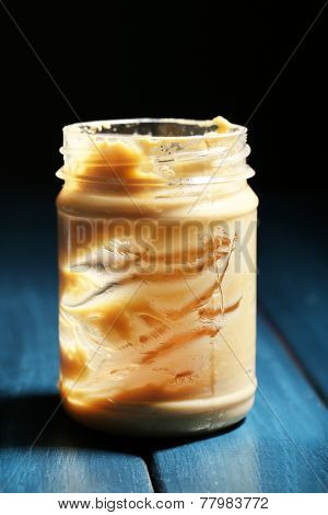 Empty peanut butter jar on table, on dark background