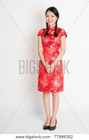 Portrait of full length Asian Chinese female, in traditional red cheongsam standing on plain background.