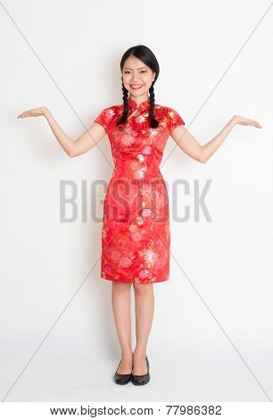 Portrait of full length Asian Chinese girl open palms with copy space, showing somethind, in traditional red cheongsam standing on plain background.