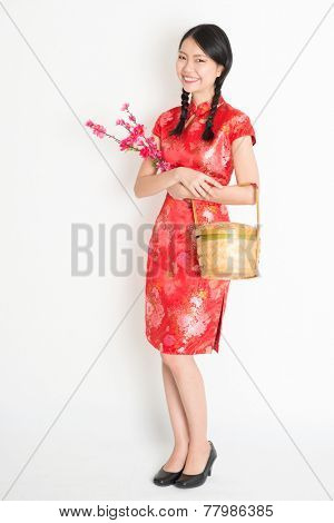 Portrait of full length Asian Chinese girl hands holding gift basket and plum blossom, in traditional red qipao standing on plain background.