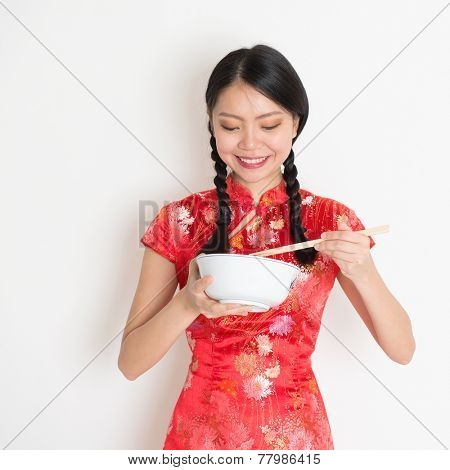 Portrait of Asian Chinese female eating, using chopsticks holding rice bowl, in traditional dress red qipao standing on plain background.