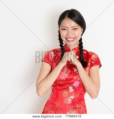 Happy Chinese New Year!! Portrait of Asian Chinese girl greeting, in traditional red qipao standing on plain background.