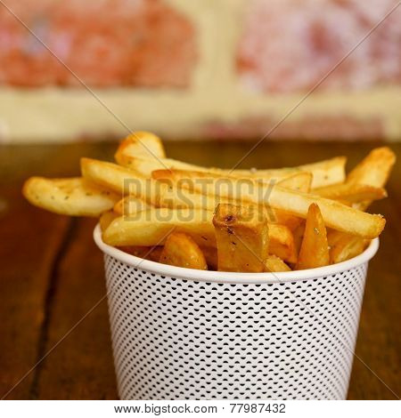 Potatoes fries in a white paper bag on wooden board