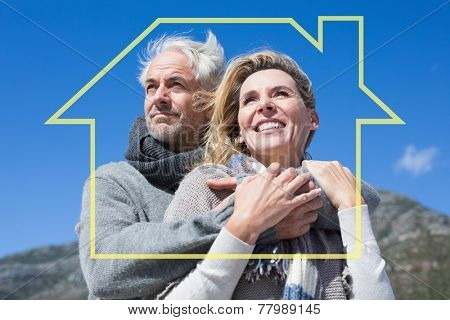 Carefree couple hugging in warm clothing against house outline