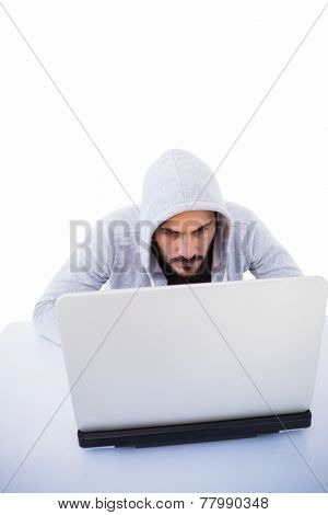 Serious burglar hacking into laptop on white background
