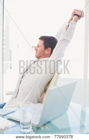 A businessman stretching in swivel chair in his office