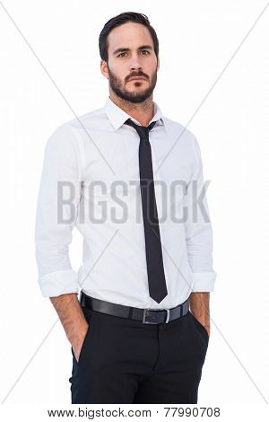 Unsmiling businessman standing with hands in pockets on white background