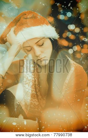 Festive brunette feeling sad at christmas against candle burning against festive background